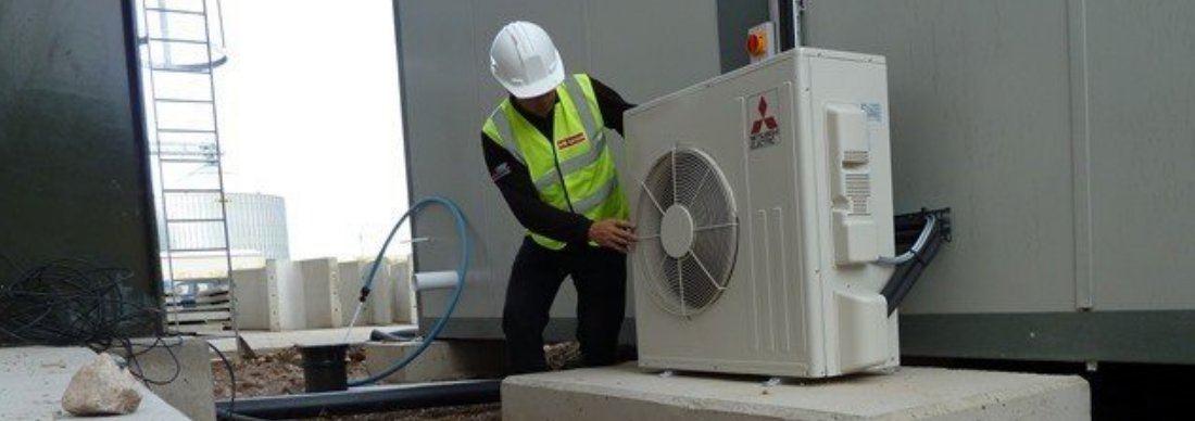 Andrew Bourner inspecting an industrial roof unit.